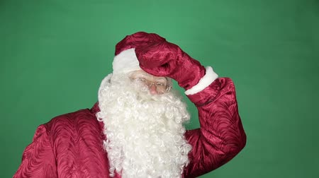 santa : Santa Claus looks around. On a green background, Santa Claus.