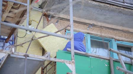 installation lectrique : Workers warm and repair the facade of the building. The old house is compacted with mineral wool and the exterior of the building is lined. Work at height without insurance