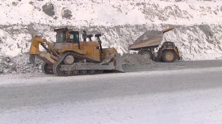 carvão gigante : Dump truck unloads stones from the body next to the tractor. Work techniques in a quarry for the extraction of chrysotile asbestos. Stock Footage