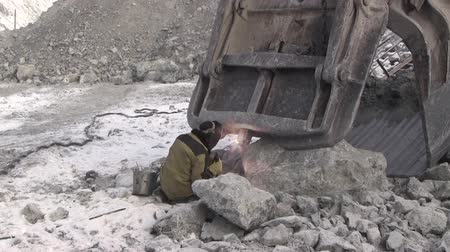 carvão gigante : A working metal welder works in a quarry. The worker in the welding mask and overalls with the help of an electrode repair the excavator bucket. Stock Footage