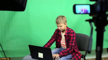 subscribers : Young boy blogger records video on a green background Stock Footage