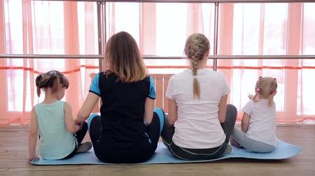 Family yoga and gymnastics at the window. Stok Video