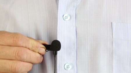 A person fixes a small microphone with a buttonhole to the shirt.