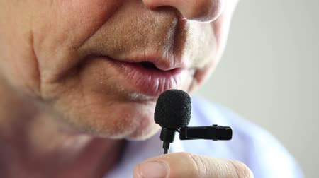 The man speaks into a small microphone in a low voice.