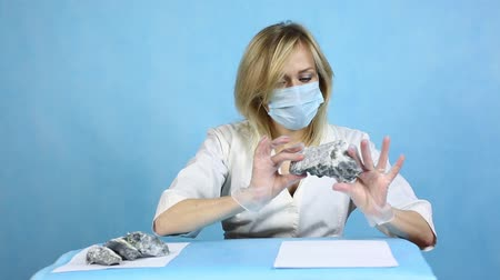 analyzes : The girl laboratory technician examines samples of minerals. Anilization asbestos. Stock Footage