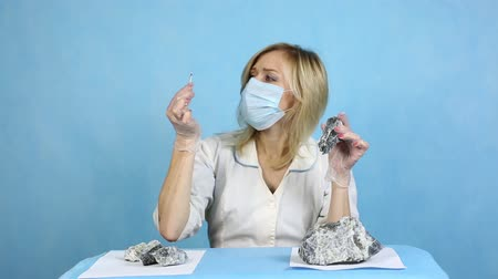 analyzes : The girl laboratory technician examines samples of minerals. A woman lab worker examines the stones with harmful asbestos. Stock Footage