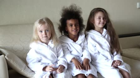 próximo : Three girls of different nationalities are sitting on the couch. Little girls in white coats are sitting next to each other and hugging.