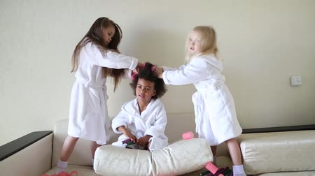 diferença : Black girl wind curlers in her hair. Little girls play with hair curlers and hairpins. Stock Footage