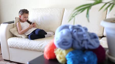 bordado : A girl with a mobile phone on the couch. There are threads for knitting in different colors. Stock Footage