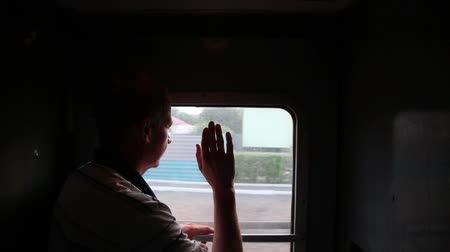 sáně : A man looks out the window. The passenger stands in the rails and sleepers.