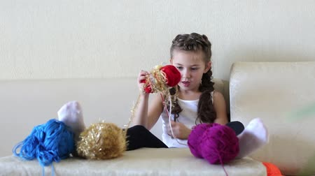 creator : The girl is coiling the thread. A little girl sitting on the couch is knitting into a ball.