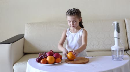 апельсины : The child slices an orange with a knife. For making cocktails