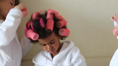 girl in robe : Dark-skinned girl with hair curlers. Beautiful black girl with red hairpins in her hair.