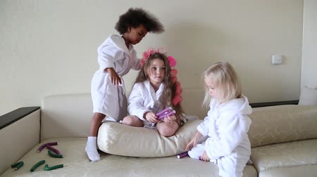 girl in robe : Little girls play with hair curlers and hairpins. Coats braids and girls hair clips