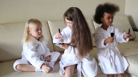 ruj : Little girls play with makeup while sitting on the couch. Girls of different nationalities. Stok Video