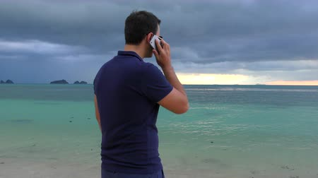 oppression : Man talking on his smart phone on the beach in cloudy dark weather