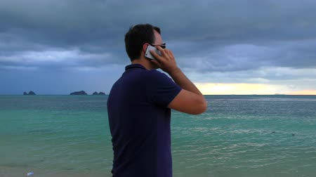grim : Man talking on his smart phone on the beach in cloudy dark weather