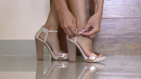 fasteners : Female legs in stylish high-heeled shoes fastening of shoes