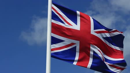 "zvedák : The ""Union Jack"", the United Kingdom flag waving in the wind in a clear, sunny day"