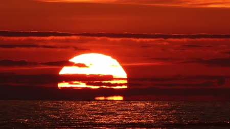 gyorsul : An iconic sunset over sea with a great, tele shot sun falling from a red and cloudy sky into the sea Stock mozgókép