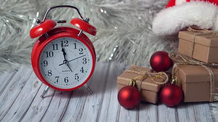 garlands : Red vintage alarm clock and three gift boxes on a wooden table decorated with a garland and red Christmas balls for the New Year or XMAS. Copy space Stock Footage
