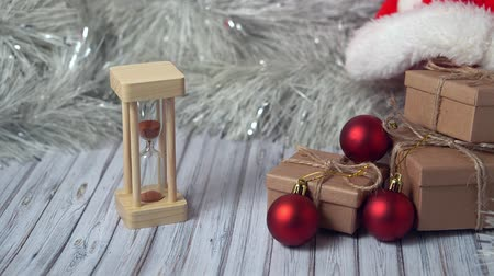sierlijst : Hourglass and cardboard box on a wooden table decorated with a garland and red Christmas balls for the New Year or XMAS. Mail, courier or delivery service concept. Copy space