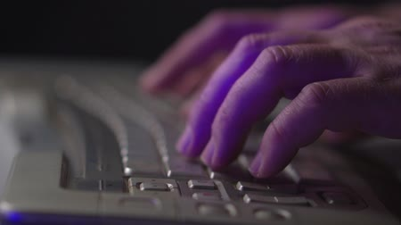 girmek : A man working at a computer. Male hands and computer keyboard closeup. Side view