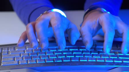kajdanki : Male hands in handcuffs and computer keyboard close up. Front view