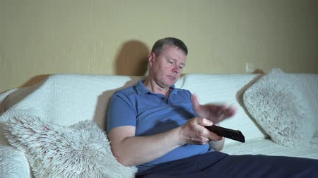 кризис : Nervous viewer. White man knocks on a faulty remote control from the TV Стоковые видеозаписи