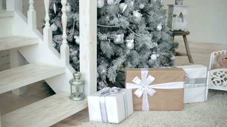подарок : Girl tries to be quiet by placing a gift under the Christmas tree