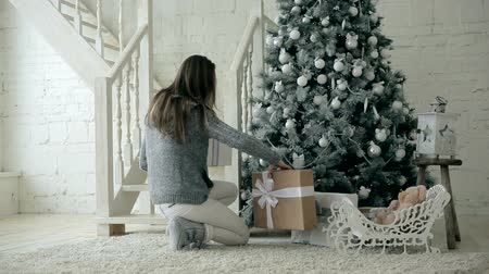 ünnepies : Beautiful girl down the stairs with Christmas presents and arranges them under the tree Stock mozgókép