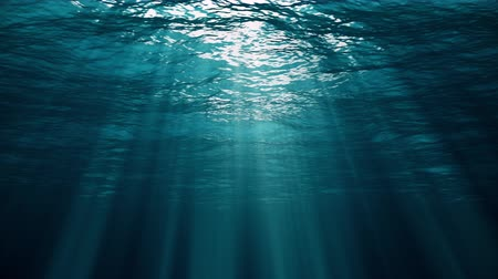 Underwater view with ocean waves flowing in the clear blue water. Beautiful aquatic view with sunbeams shining and creating god rays in the deep sea. 3D animation with swells and tidal waves