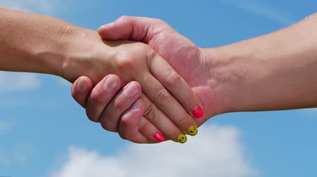 souhlasit : A man and woman shaking hands on blue sky background