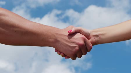 сильный : A man and woman shaking hands on blue sky background