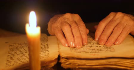 religioso : Elderly woman reading old book by candlelight