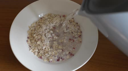 sightly : Instant oatmeal with raspberries in natural lighting. Pouring water and stirring by spoon. Stock Footage