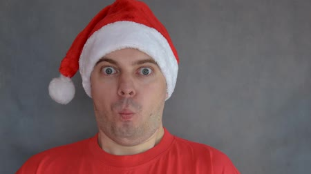 csodálkozás : Young man in red santa hat  - surprised face. Stock mozgókép