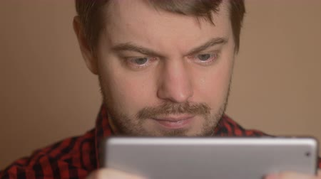 výrazy : Young man looking at a tablet - the emotion of surprise.