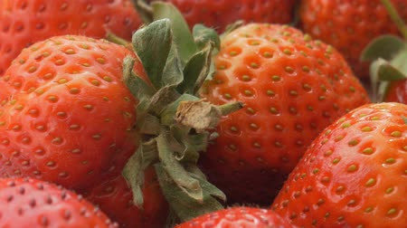 Natural looking fresh red strawberry. Macro with shallow depth of field. Stok Video