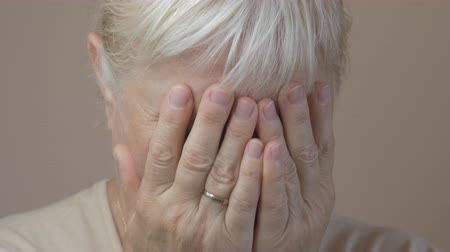 regret : Closeup of aged woman crying.