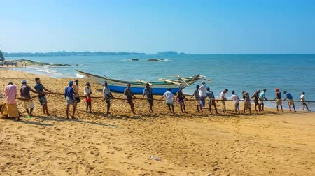 bentota : BENTOTA, SRI LANKA - DECEMBER 6, 2016: The crew of fishermen manually pulls their net out of the ocean, standing on the fine sand beach, on December 6 in Bentota.
