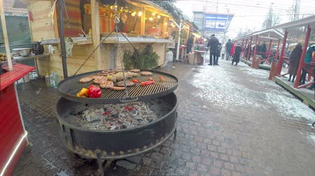 cop : KIEV, UKRAINE - JANUARY 4, 2017: The grill at Christmas Market with fragrant sausages, frankfurters, potato on skewers and peppers attracts visitors with delicious smell, on January 4 in Kiev. Dostupné videozáznamy