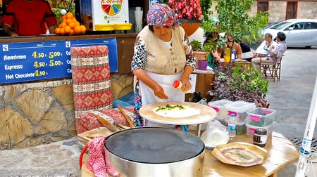 antalya : The senior woman - the cook of the restaurant, prepares gozleme, traditional Turkish village flatbread, she kneads and rolls out dough, while prepared flatbread is heated on griddle, Antalya, Turkey.