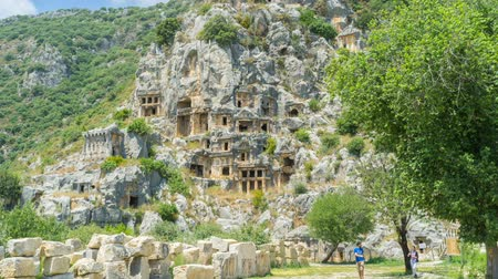 sarcophagus : Archaeological site of Myra with preserved Lycian tombs, cut in rock and surrounded by green trees, Demre, Turkey. Stock Footage