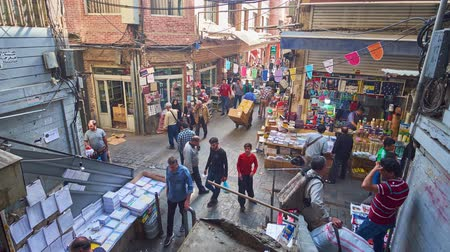 porters : TEHRAN, IRAN - OCTOBER 11, 2017: The open air intersection of Grand Bazaar, this area is always crowded, full of clients, vendors and porters, on October 11 in Tehran. Stock Footage