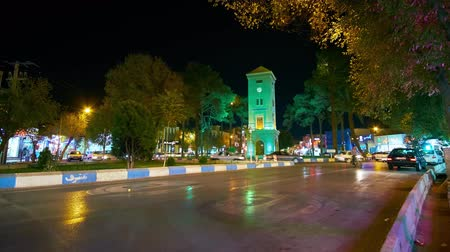 yazd : YAZD, IRAN - OCTOBER 17, 2017: Time lapse of traffic on Markar square with a view on clocktower in evening lights, on October 17 in Yazd