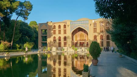 ispahan : ISFAHAN, IRAN - OCTOBER 19, 2017: The walk along the pond in garden of medieval Chehel Sotoun Palace, one of the notable city landmarks, on October 19 in Isfahan. Stock Footage