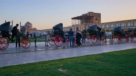 ispahan : ISFAHAN, IRAN - OCTOBER 19, 2017: The twilight over the crowded Naqsh-e Jahan Square, the popular place for the walks among locals and tourists, enjoying the horse carriages, on October 19 in Isfahan.