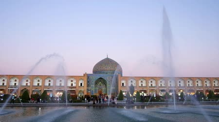 ispahan : ISFAHAN, IRAN - OCTOBER 19, 2017: The patterned dome and bright blue tiled portal (iwan) of Sheikh Lotfollah Mosque behind the fountains in crowded Naqsh-e Jahan square, on October 19 in Isfahan. Stock Footage