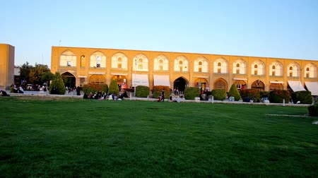 ispahan : ISFAHAN, IRAN - OCTOBER 19, 2017: Panorama of Naqsh-e Jahan square, locals enjoy picnics on the lawn, play active games and relax in heart of medieval architectural ensemble, on October 19 in Isfahan.